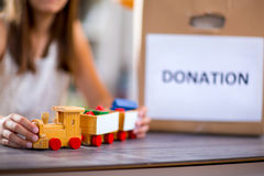 Girl  taking toy for donation Royalty Free Stock Photography