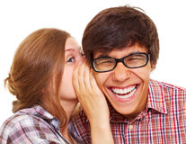 Girl talking in boy's ear stock photography