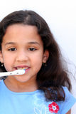 Girl Talking Brushing Teeth. Young girl is brushing her teeth in bathroom Royalty Free Stock Photos