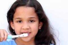 Girl Talking Brushing Teeth. Young girl is brushing her teeth in bathroom Royalty Free Stock Images