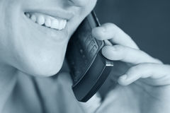 Girl talking on cell phone. Woman smiling with cell phone up to her ear. High key, focus on whole subject royalty free stock image