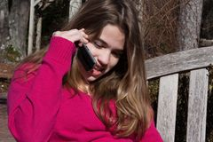 Girl talking on cell phone. Young beautiful girl outside on bench talking on a wireless phone Stock Image