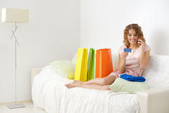 Girl talking on cell phone with credit card royalty free stock photography