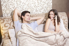 Girl talking on the cell phone while laying with his boyfriend. In the bed stock images