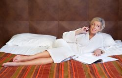 Girl talking on cellphone. Relaxed girl lying on the bed and talking on cellphone with magazine Stock Photos