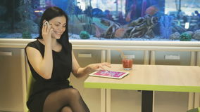 Girl talking with friend using a mobile phone. Girl sitting at a cafe and talking with friend using a mobile phone in the background blue aquarium stock footage