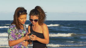 Girl talking with her best friend and looking at the smart phone on the beach. Girl talking with her best friend and looking at the smart phone stock video footage