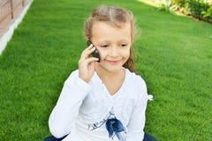Girl talking on mobile phone. Little cute girl talking on a mobile phone while sitting on green grass Stock Image