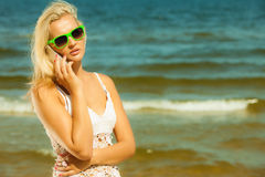 Girl talking on mobile phone on beach Stock Photos