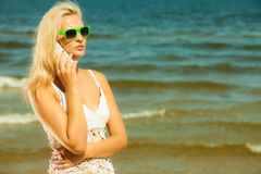 Girl talking on mobile phone on beach Stock Photos