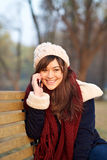 Girl talking on mobile phone on bench in park Royalty Free Stock Photography