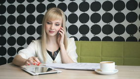 Girl talking on mobile phone during coffee break. Girl aged 20s sitting in a cafe talking on mobile phone and writes text on paper during coffee break stock footage
