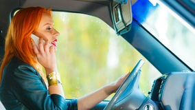 Girl talking on mobile phone while driving the car. Royalty Free Stock Image