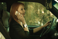 Girl talking on mobile phone while driving the car. Stock Photo