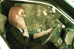 Girl talking on mobile phone while driving the car. Royalty Free Stock Photography