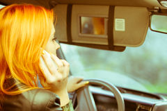 Girl talking on mobile phone while driving the car. Royalty Free Stock Photo