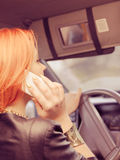 Girl talking on mobile phone while driving the car. Stock Image
