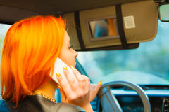 Girl talking on mobile phone while driving the car. Stock Photography