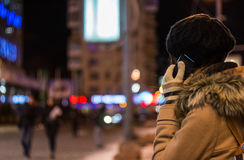 Girl talking on mobile phone at night in winter Royalty Free Stock Photo