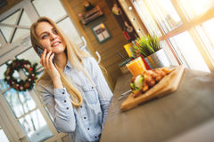 Girl talking on mobile phone and relaxing in the cozy cafe sitting at the table with the sweet waffles and orange juice. Beautiful girl talking on mobile phone Royalty Free Stock Images