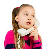 Girl Talking by the Phone. Pretty young girl talking by the corded telephone, isolated Stock Images