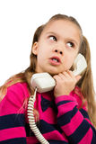 Girl Talking by the Phone. Pretty young girl talking by the corded telephone, isolated stock photography
