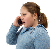 Girl Talking On The Phone. A young girl talking on a cell phone, isolated against a white background Stock Images