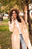 Girl talking on the phone in the autumn park stock photos