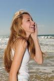 Girl talking on phone on the beach. Woman talking on phone on the beach stock photography