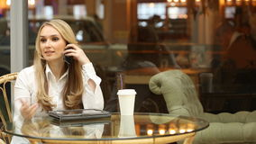 Girl talking on the phone in a cafe. waving his stock video footage