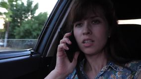 Girl is talking on phone and driving by car on city road with an open window. Close-up stock footage
