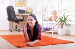 Girl talking on phone on the floor Royalty Free Stock Photos