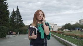 Girl talking on the phone. The girl goes down the avenue and talking on the phone stock footage