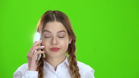 Girl is talking on the phone . Green screen stock footage