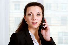 Girl talking on the phone and looking at camera Stock Images