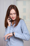 Girl talking on the phone and looking at her watch Royalty Free Stock Image