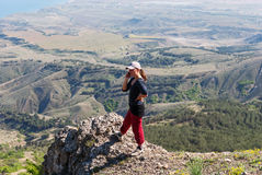 Girl talking on the phone in the mountains. Girl talking on the phone while standing on the edge of a cliff Royalty Free Stock Image