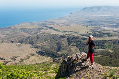 Girl talking on the phone in the mountains. Girl talking on the phone while standing on the edge of a cliff Stock Photography