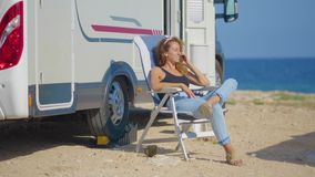 The girl talking on the phone near her motorhome. Traveling woman by mobile motor home RV camper van. The girl talking on the phone near her motorhome stock footage