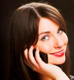 Girl talking on the phone over black. Beautiful girl talking on the phone over blackrr Stock Photo