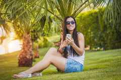 Girl is talking on the phone in the palm garden Stock Images