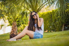 Girl is talking on the phone in the palm garden Stock Photography