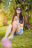 Girl is talking on the phone in the palm garden Stock Image