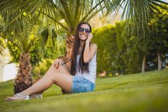 Girl is talking on the phone in the palm garden Royalty Free Stock Photo