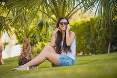 Girl is talking on the phone in the palm garden Royalty Free Stock Photography
