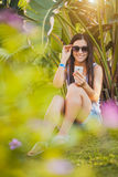 Girl is talking on the phone in the palm garden Royalty Free Stock Image