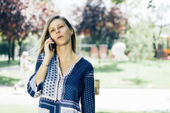 Girl talking on the phone. In a park Royalty Free Stock Photo