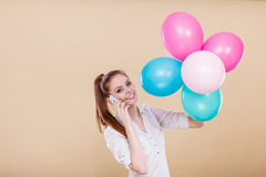 Girl talking phone while playing with balloons Royalty Free Stock Photography