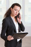Girl talking on the phone while reading information Royalty Free Stock Photos
