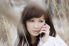 Girl talking on the phone in the reed Stock Photo